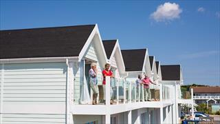Carousel Item 6: Guests on their balconies at Corton Coastal Village.