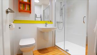 Carousel Item 4: Cream and yellow bathroom with walk in shower