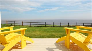 Carousel Item 5: Two yellow lounge chairs on a patio facing out to the sea