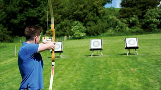 Carousel Item 4: A member of team aiming at an archery target