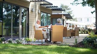 Carousel Item 3: A pair of guests drinking wine on the patio outside their Garden lodge