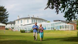 Carousel Item 6: Two guests walking across the beautiful grounds of Gunton Hall